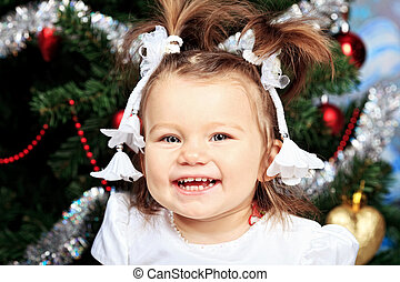 laughing child - Beautiful child sitting against Christmas...