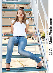 Beautiful girl sitting on the airplane gangway shooting...