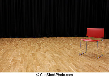 A directors chair on a stage with a blackcurtain in...