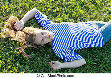 beautiful girl in the shirt on the grass outdoors shooting