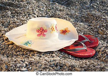 hat and flip-flops on the stones outdoors shooting