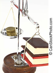 Money and books on balance scale