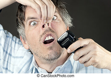Man Trims Nose Hair - Cloe-up of a man attempting to trim...