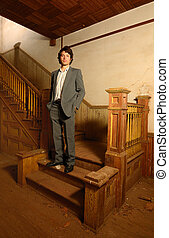 Man on Stairs in an Old House - Msn in suit standing on the...