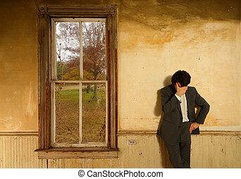 Man in Despair - Man wearing a suit in despair props his...