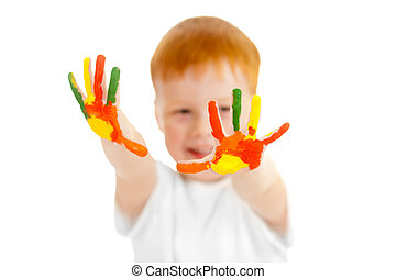 Adorable redheaded boy with focus on hands painted in bright colors