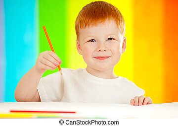 Red-haired adorable boy drawing with orange pencil on...