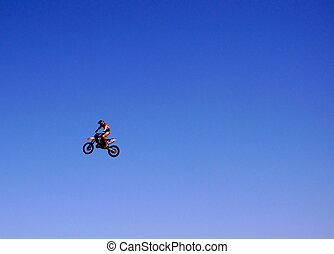 A motor bike rider in the air - a motor bike rider jumping...
