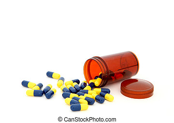 close up of isolated capsules spilling out from small bottle