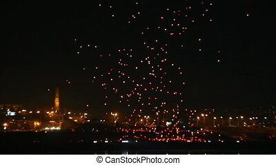 many Japanese Lantern flies over city at night