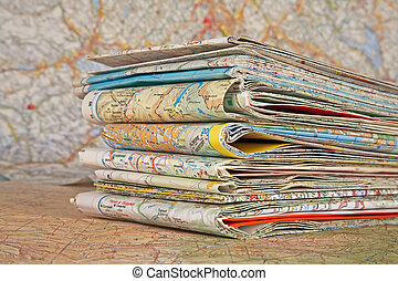 various travel maps - stack of various travel maps on a open...