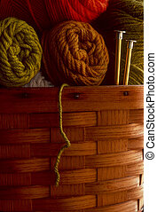 Wool yarn in a basket with knitting needles - Skeins of wool...