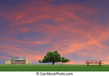 An outdoor restroom facility and a large oak tree with picnic tables at a park on a summer day with a gorgeous sunset red sky with room for your text.