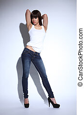 Beautiful mixed race woman in jeans and white vest