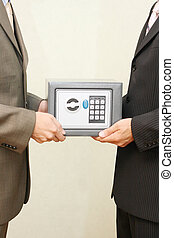Safe - Two businessmen holding a steel safe