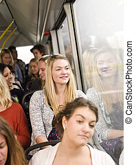 Happy woman on the bus with large group of people