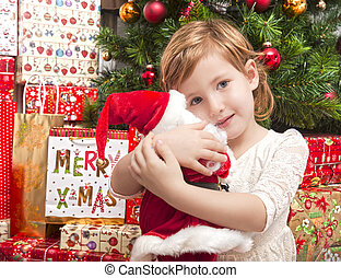 Child with santa doll in front of christmas tree - Cute...