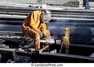 Welder in work - Worker with protective mask and gloves...