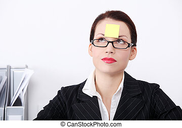 Thinking businesswoman with post it note on her forehead. -...