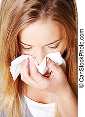 Attractive blond woman using a tissue.