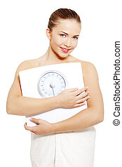 Diet concept - Portrait of a young woman holding a scale