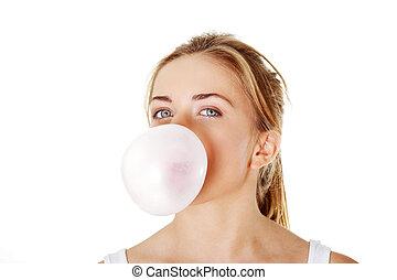 Teen woman blowing bubble gum - Young beautiful woman...