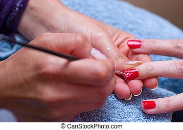 Nail art - Beautician at work, decorating shiny red nails