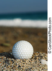 Golf Ball On The Beach, Ready To Be Hit In To The Ocean.