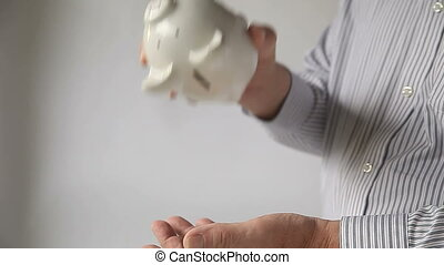 businessman shakes piggy bank - close up of a mans hands...