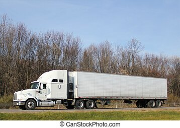 Tractor-trailer truck traveling along an interstate highway