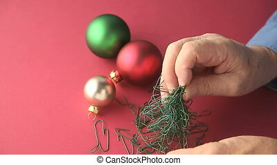 untangling Christmas ornament hooks - close up of a mans...