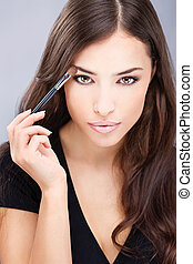 pretty black hair woman applying make up with brush in her right hand