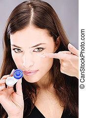 Young woman holding contact lenses cases and lens in front...