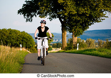 cycling woman - A cycling woman in front of rural landscape