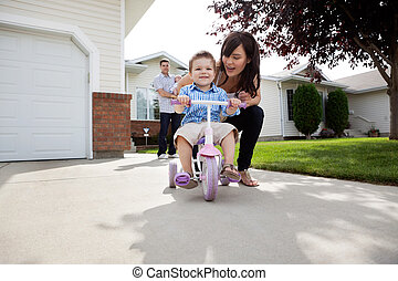 Mother Teaching Son To Ride Bike - Beautiful happy young...