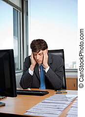 Stressed Businessman - Stressed business manager sitting at...
