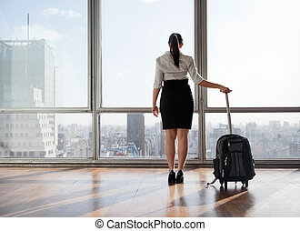 Businesswoman With Luggage Trolley - Rear view of business...