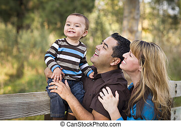 Happy Mixed Race Ethnic Family Playing In The Park - Happy...