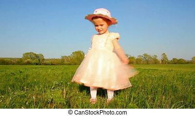 happy little girl in dress on meadow