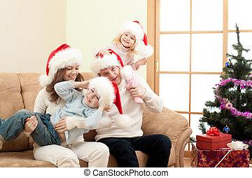happy family in Christmas Santa's hats on sofa in living room
