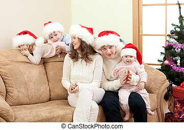 happy family in Christmas Santa's hats on sofa in living...