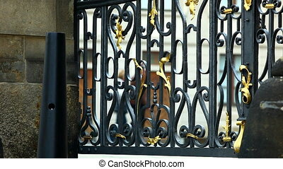 Metal fence on gate and tourist walk at background