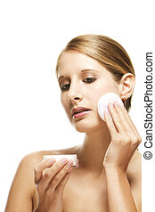 young woman applying makeup on white background
