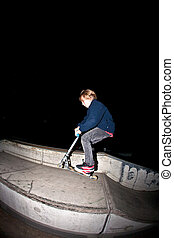 young boy jumpy with his scooter by night