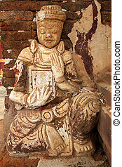 Seated Buddha - White seated Buddha and red brick wall in...