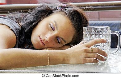 Drunk young woman with beer buck - Young woman asleep...