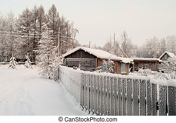 Winter season in Russian village. Snow covered buildings and...