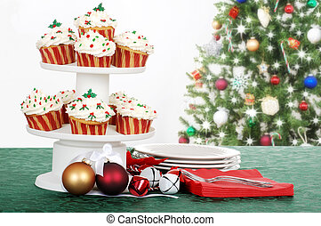 holiday cupcakes with decorations and tree in the background...