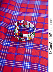 Colorful African bracelet with Masai blanket background