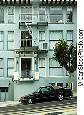 Facade of a green building and the automobile in the street...